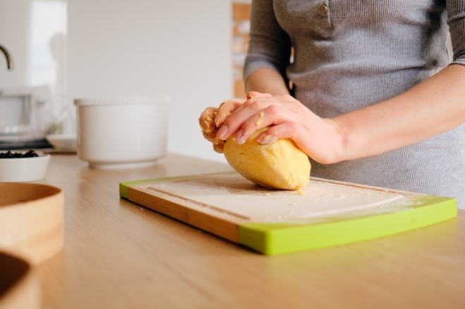 Person preparing dough on a sunny day. Homemade bread, bakery while staying home.